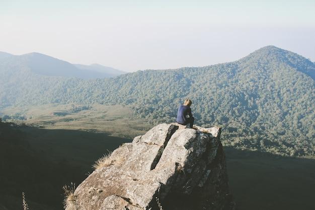 タイのカラフルな夏の山々で素晴らしい景色を見ている丘の上の男