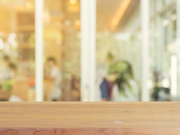 ぼんやりとした背景の前に木製ボードの空のテーブル
