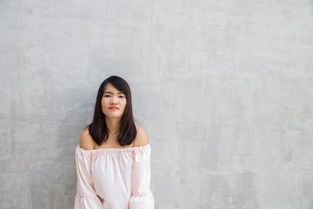 コンクリートの壁に対して幸せな若い女。