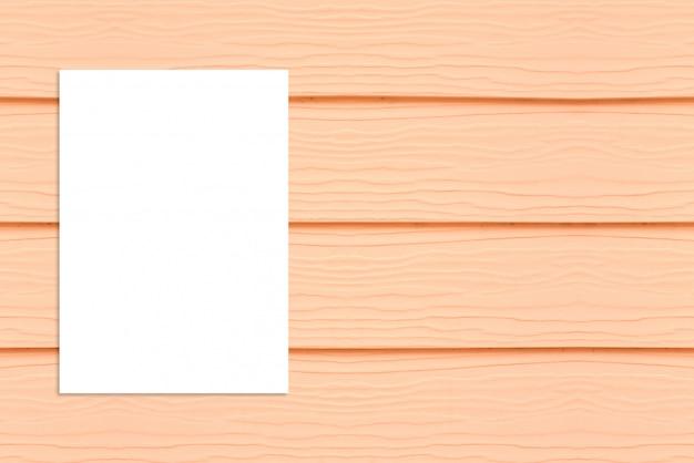 木製の壁に掛かっている空白の折り畳まれた紙のポスター、あなたのデザインを追加するために模擬テンプレート。