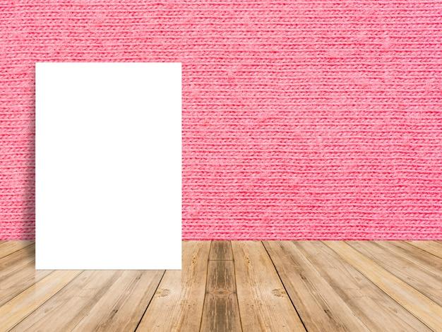 赤い布の壁と熱帯の木のテーブルの上にもたれて空白の白いポスター。