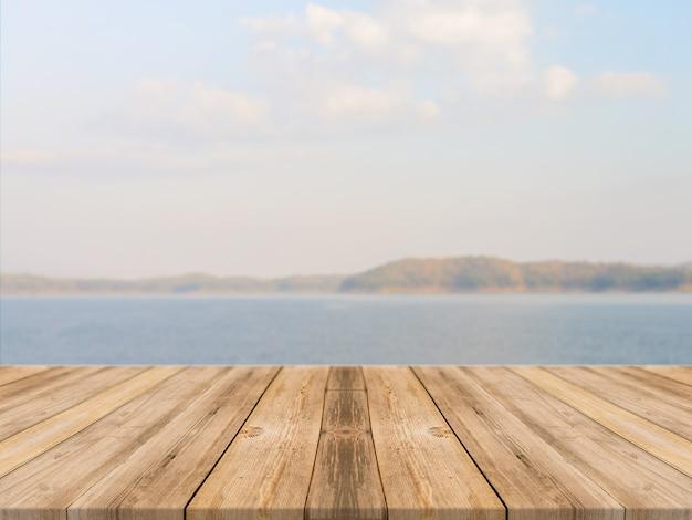 青い海&空の背景の前にヴィンテージの木製ボード空のテーブル。