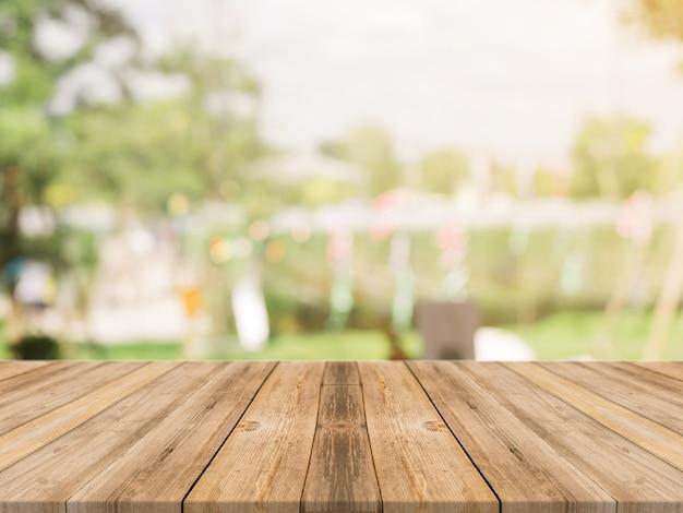 木の板の空のテーブルは、コーヒーショップのバックグラウンドでぼかし。