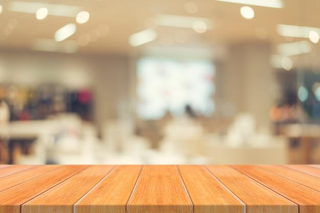 木の板の空のテーブルは、カフェバックグラウンドでぼかします。
