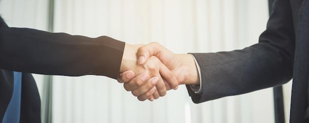 仕事を交渉する、イメージ経済人の握手、仕事に満足している彼女、仕事の仲間と楽しんでいるビジネスマン、ハンドシェイクジェスチャー人のコネクションディールコンセプト。