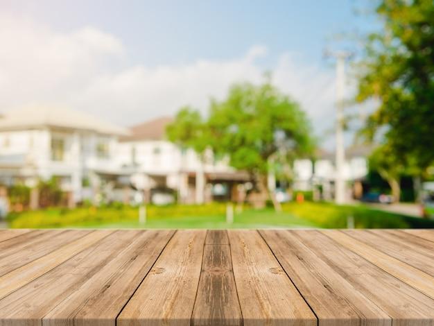 ぼかしの上に空の木のテーブルトップ庭と朝の背景に家からの抽象的な緑。モンタージュ製品の表示やデザインのキーの視覚的レイアウト
