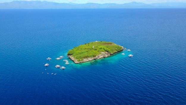Вид с воздуха на песчаный пляж с туристами, плавающими в красивой чистой морской воде пляжа сумилонского острова, приземляющегося около ослоба, себу, филиппины. - увеличьте цвет обработки.