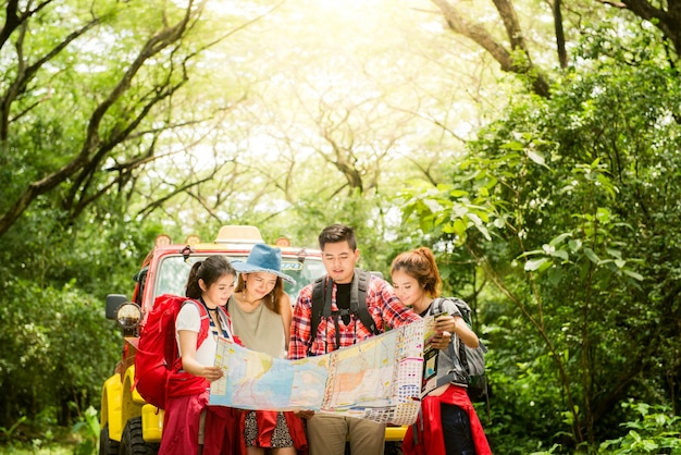 ハイキング - 地図を見ているハイカー。一緒にナビゲートしているカップルや友達キャンプ中に幸せに笑う旅行旅行は、森林のアウトドアハイキング。若い、混血、アジア人、女、人。