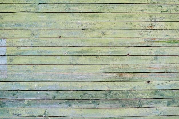 Старый деревянный расписной зеленый щит с трещинами и царапинами