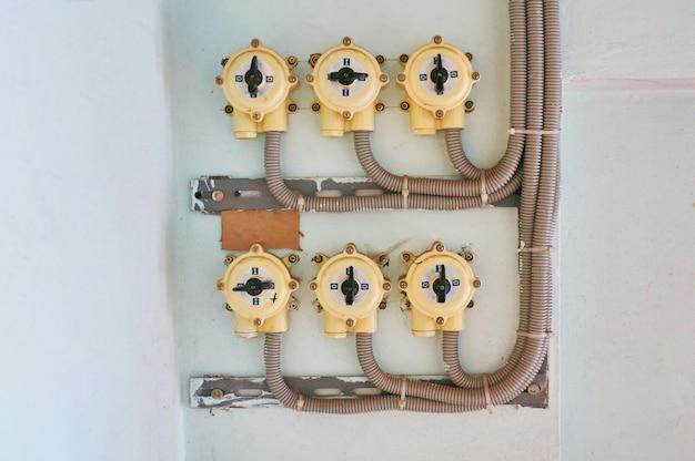 ケーブルが接続された白い漆喰壁の電気スイッチ。