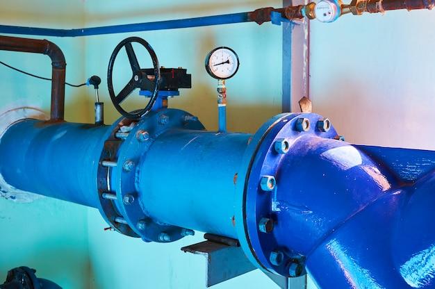 青く塗られたパイプに取り付けられたゲートバルブ。産業の背景。