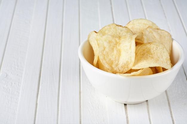 白い木製の背景に白いボウルにおいしいゴールデンポテトチップス。