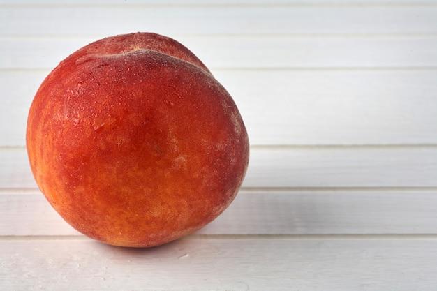 白い木製の背景においしい桃。