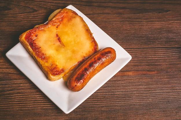 溶けたチーズと揚げソーセージのサンドイッチ