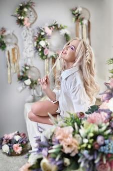 花を持つ華やかなブロンドの女の子。