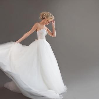 豪華なウェディングドレスで若い花嫁を踊る。白のきれいな女の子。幸福、笑いと笑顔、灰色の背景の感情