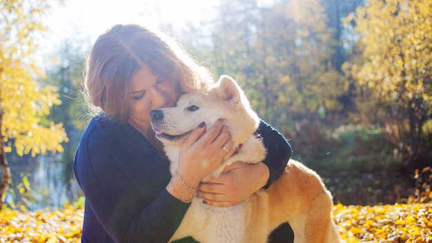 Молодая женщина на прогулке со своей собакой породы акита ину