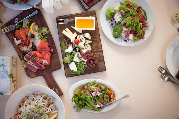 Закуски, тапас и салаты на деревянной доске. сервировка стола в ресторане