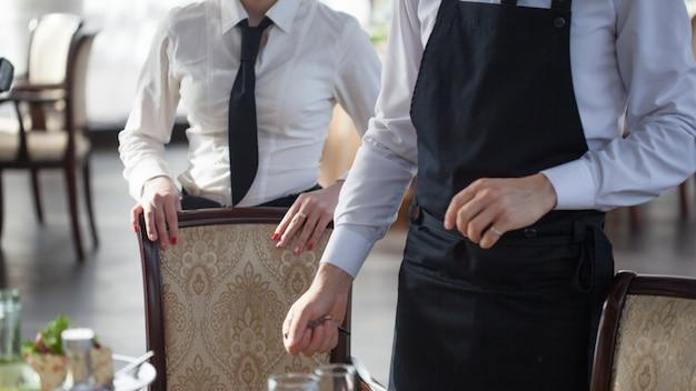 Официанты в ресторане, накрывают на стол