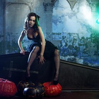 Молодая и сексуальная женщина, образ ведьмы на кладбище, сидя на крышке гроба.