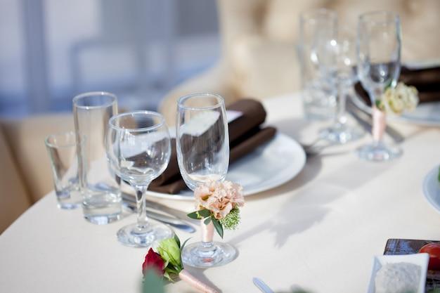 Сервировка стола в ресторане. цветочный декор на бокалах, свадьба
