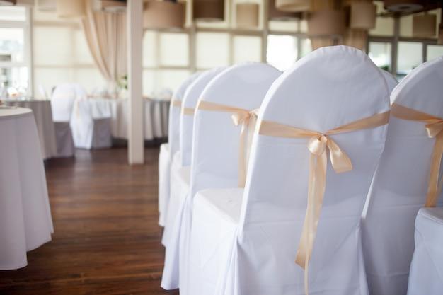 Украшенные стулья в ресторане, много подряд, готовимся к празднику