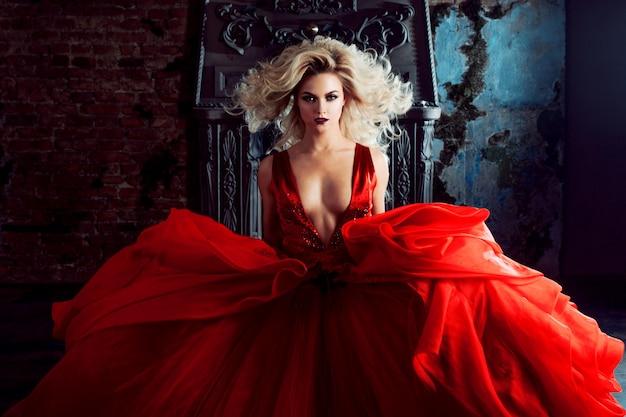 若い壮大な女性のファッション写真。カメラに向かって実行しています。ふわふわのスカートと赤いドレスの魅惑的なブロンド