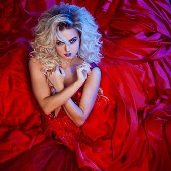 赤いドレスの若い壮大な女性のファッション写真。スタジオポートレート