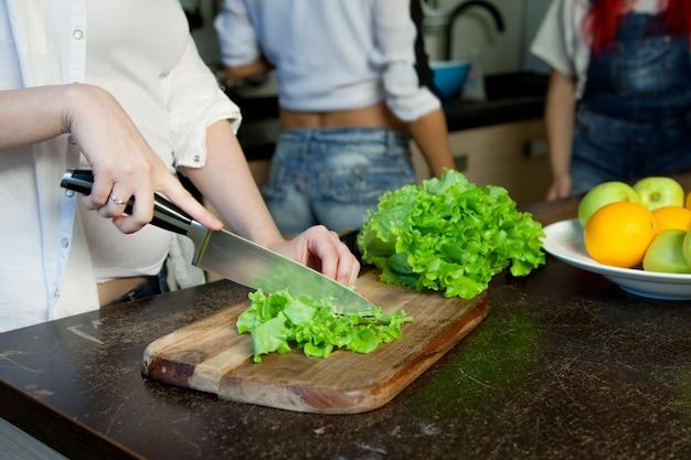 夕食、キッチンでまな板の上のレタスを準備する女性主婦の手