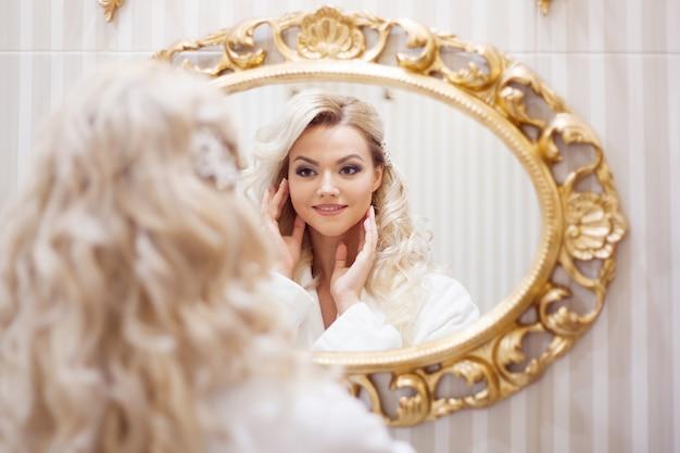 鏡を見てバスローブの若いセクシーな女性の肖像画。