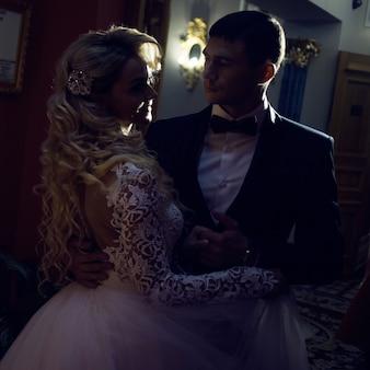美しい若いカップル、新郎新婦。豪華なインテリア。ダークトーンの親密な雰囲気