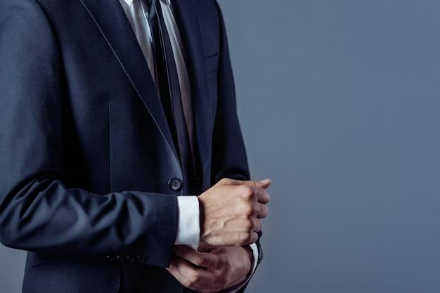 Человек в костюме на сером, руки крупным планом
