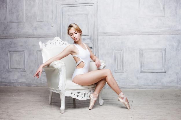 白いダンスレオタードとポワントシューズの若い美しい女性