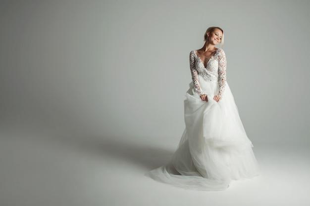 Красивая невеста в свадебном платье с длинной пышной юбкой на белом