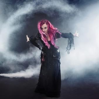 Женщина с рыжими волосами в костюме ведьмы, стоя вытянутыми руками, сильный ветер