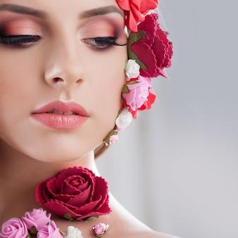 Красивая молодая девушка с аппликацией цветами на лице.