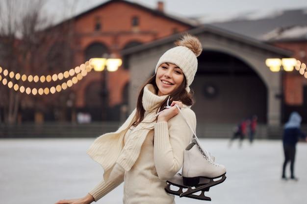 Очаровательная молодая женщина в парке возле катка.