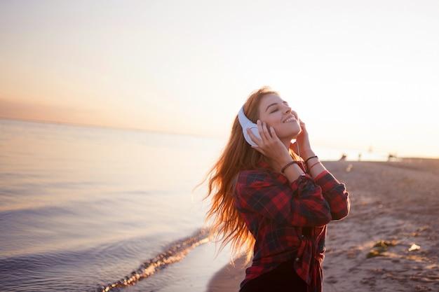 Молодая женщина с наушниками, меломан на пляже