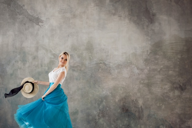 Красивая молодая женщина в пышной синей юбке, кружение и танцы. летний стиль, соломенная шляпа с черной лентой.