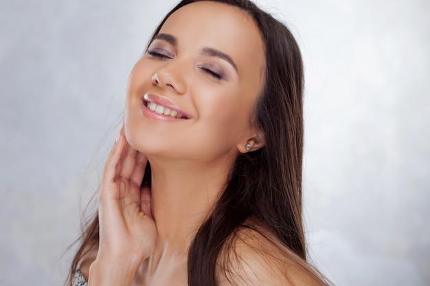Молодая обаятельная брюнетка улыбается. портрет красоты молодой красивой женщины