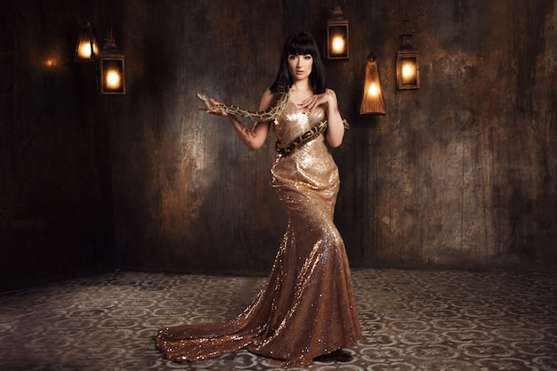 ゴールドドレスとヘビの美しく神秘的なブルネット