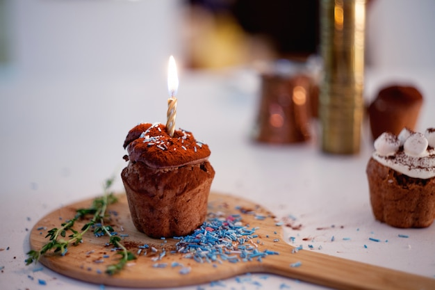 Вкусный день рождения кекс со свечой на столе, размыты