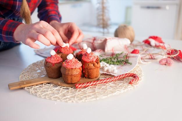 女の子は新年のお祝いのカップケーキ、テーブルの上のチョコレートのマフィンを飾る