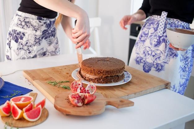 Две девушки делают торт на кухне. женские руки, наносящие шоколадный крем