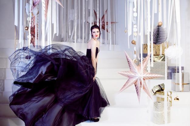 美容ブルネットモデルの女性の休日はメイクアップします。非常に長い列車と黒のドレスでエレガントな女の子