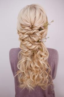 カールを織り交ぜ、花びらで飾るエレガントなトレンディなヘアスタイルの背面図