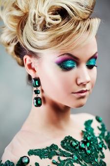 美しい緑のドレスの若い魅力的なブロンドの女性の肖像画。テクスチャ背景、インテリア。贅沢な髪型
