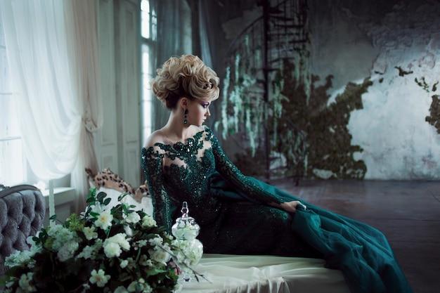 テーブルの上に座って美しい緑のドレスの若い魅力的なブロンドの女性。テクスチャ背景、インテリア。贅沢な髪型