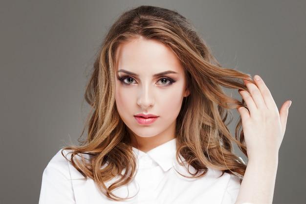 Красивая молодая женщина в белой блузке, портрет крупным планом.