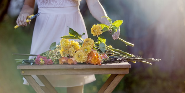 若くてきれいな女性の花屋。公園の少女は花束を描きます。アウトドア